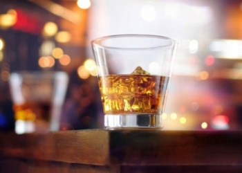 glass-of-whiskey-drink-with-ice-cube-on-table-wooden-bar-background-picture-id857015412